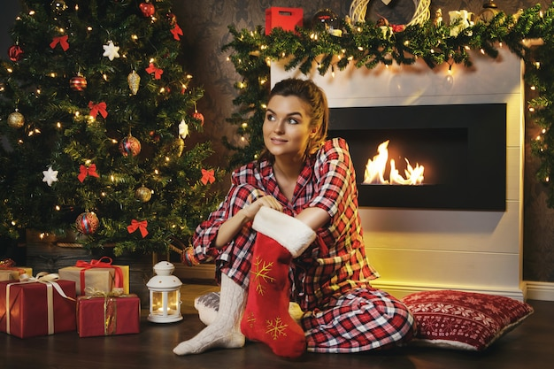 Woman searching gifts in christmas stocking