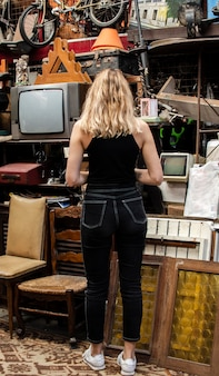 Woman searching for something to buy in an antiques market