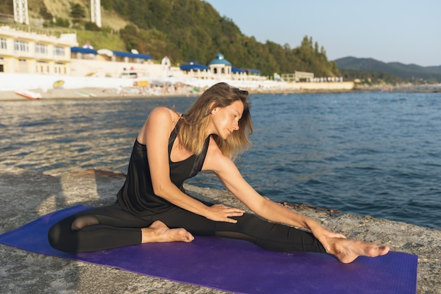 A woman on the seashore on a summer sunny evening performs a muscle stretching exercise