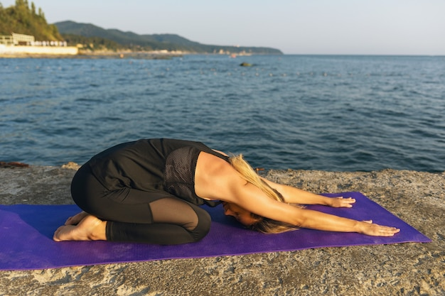 A woman on the seashore on a sunny summer evening performs the balasana exercise a resting pose