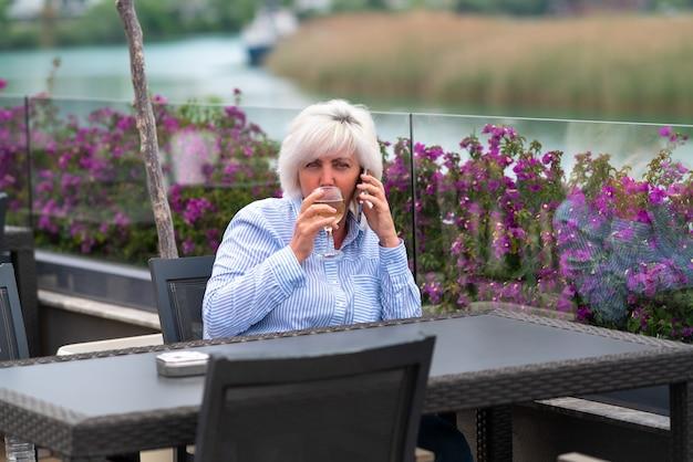 川を見下ろすレストランに座る女性
