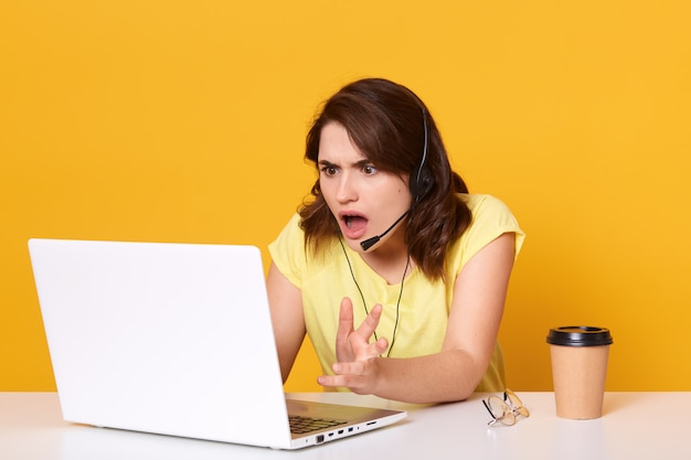 Woman seatting at table and looking at her laptop screen in consternation and horror, keeping mouth opened, wearinfcasual tshirt, posing isolated on yellow, working online.