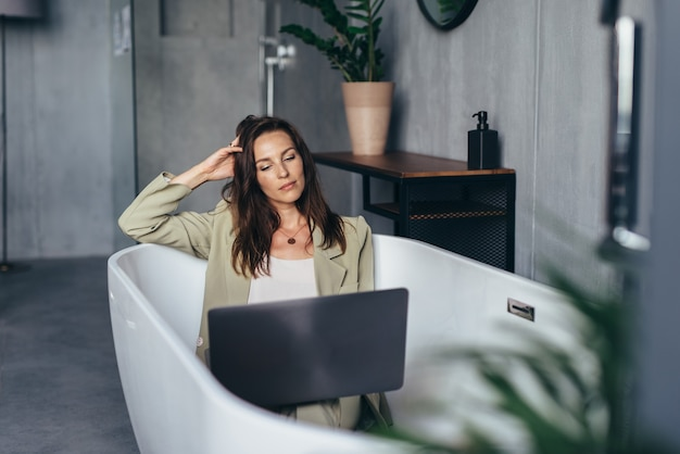 Woman secluded at home in the bathtub and works.