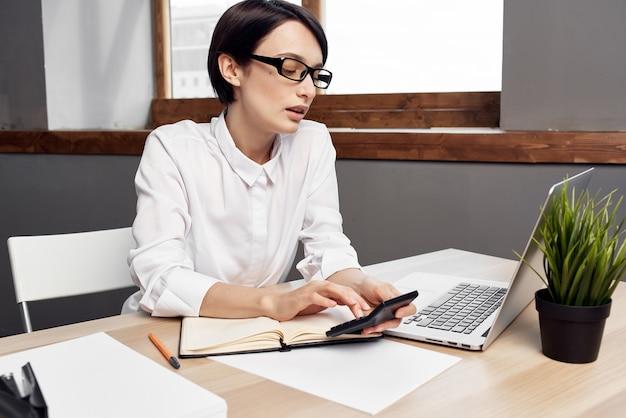 Женщина-секретарь на своем рабочем столе профессиональный офисный ноутбук