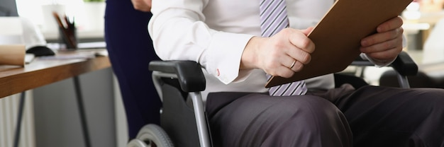 Woman secretary rolls ceo in wheelchair with documents and reports in hands