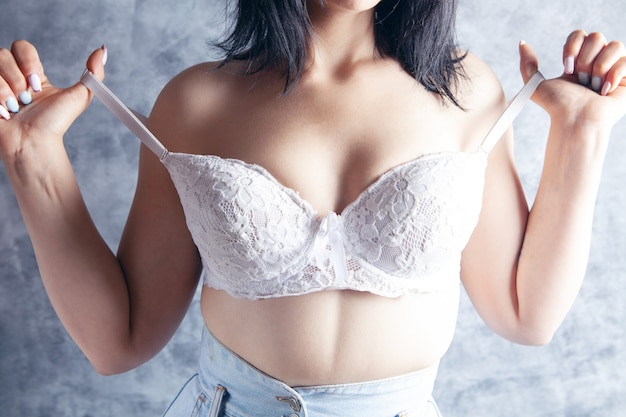Woman seductively pulling bra strap off shoulder. on gray background