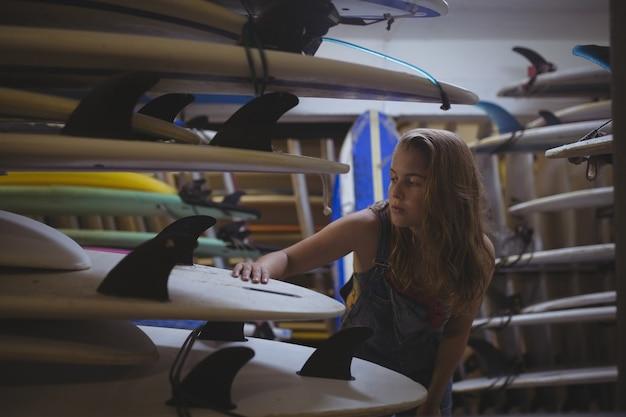 Женщина, выбирающая доску для серфинга