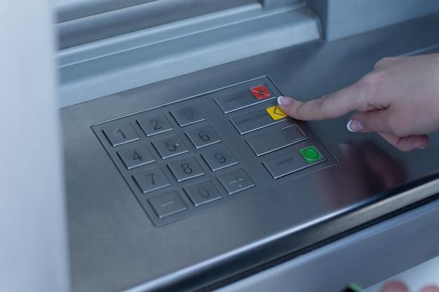 은행 atm에서 거래를 선택하는 여성은 손가락으로 노란색 버튼을 눌러 자동 입출금기에서 현금을 인출할 수 있습니다.
