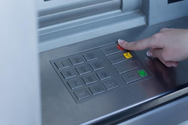 은행 Atm에서 거래 유형을 선택하는 여성이 신분증 및 핀 코드 확인을 완료하면서 손가락으로 빨간 버튼을 누르고 있습니다. 프리미엄 사진