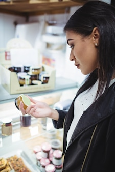 Женщина выбирая мед на прилавке еды