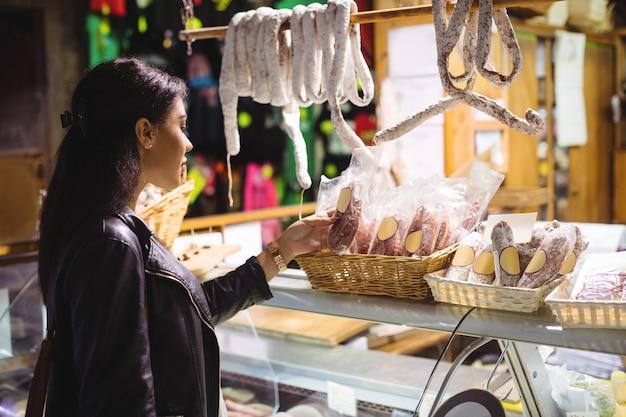 肉のカウンターでソーセージを選択する女性