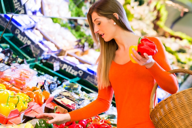 Woman selecting vegetables in grocery store