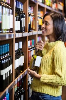 Женщина выбирает вино в продуктовом разделе