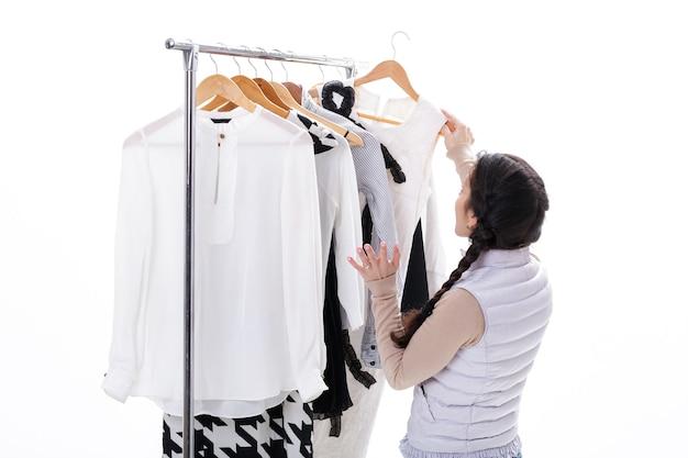 女性は白い背景の上のラックの木製ハンガーで新しいファッションの服を選択します。ショッピングのコンセプト