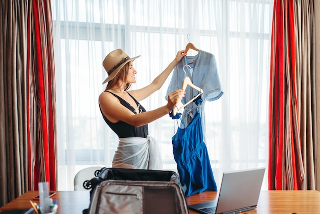 Женщина выбирает наряды в офисе, думая о путешествии.