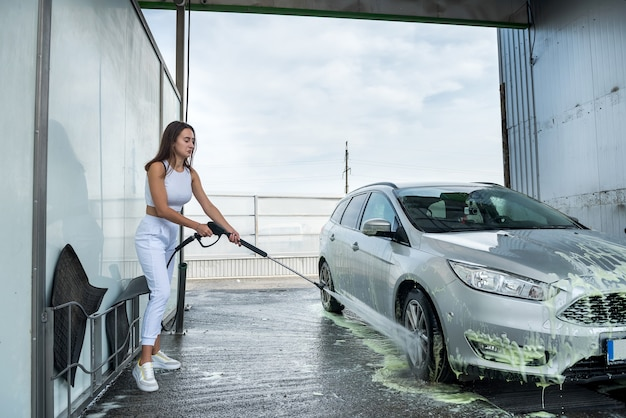 Woman at the self-service car wash station washing the foam off her car