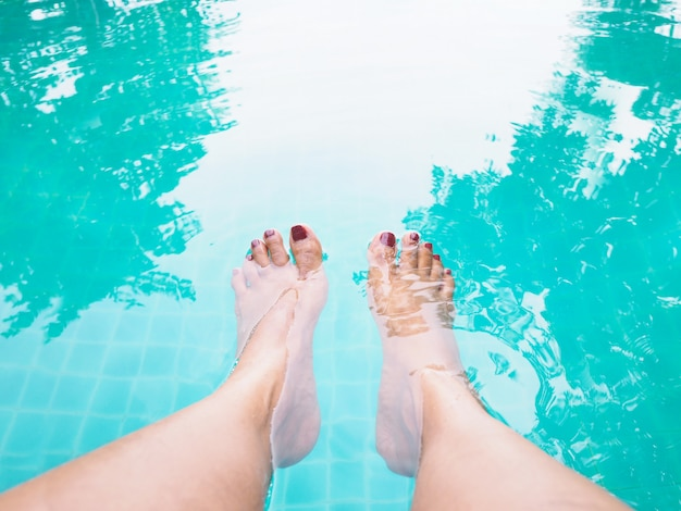 Woman selfie barefoot in the water at swimming pool