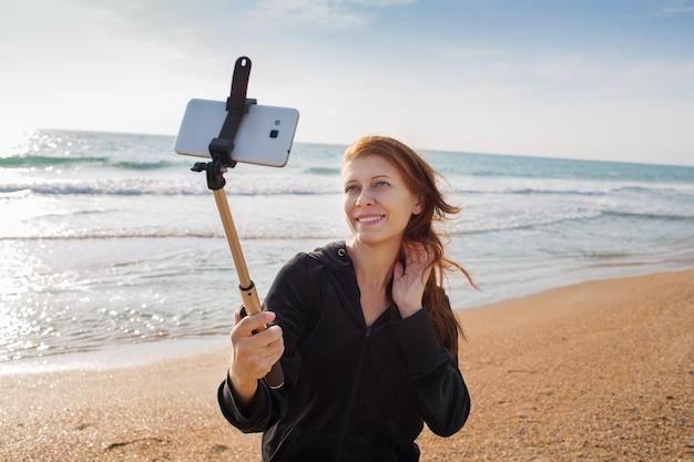 海でスマートフォンと女性の自分撮り