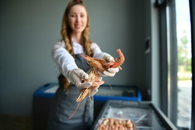 シーフード店の魚の女性売り手は、巨大なエビを持って手を伸ばします。ぼやけた魚屋の手にあるキングエビにソフトフォーカス。