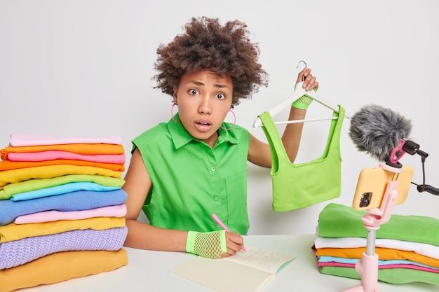 女性はオンラインで服を販売しますハンガーにクロップドトップを保持しますメモ帳に情報を書き留めます白で隔離された折り畳まれた洗濯物のスタックでテーブルに座っています