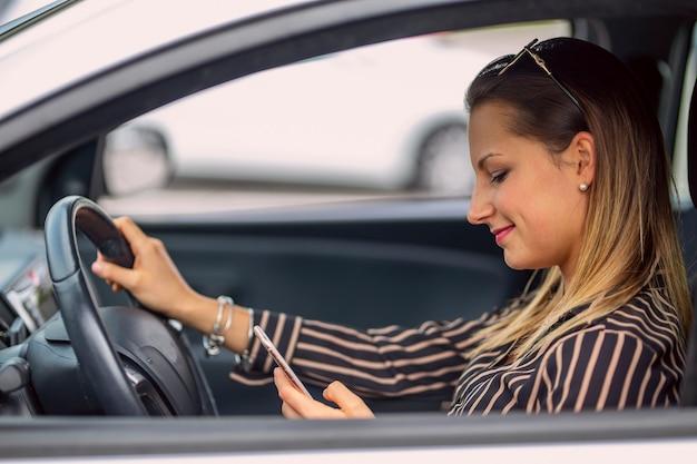 車に座って携帯電話でメッセージを送る女性
