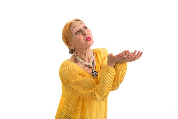 愛の白い背景ジェスチャーで空気キス年配の女性を送信する女性