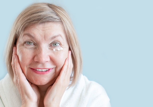 Улыбка старшего женщины с лосьоном против старения. натуральные спа-процедуры, концепция ухода за телом, органическая косметика. концепция против старения, здравоохранение и косметология, пенсионеры и пожилые люди, новые пожилые люди