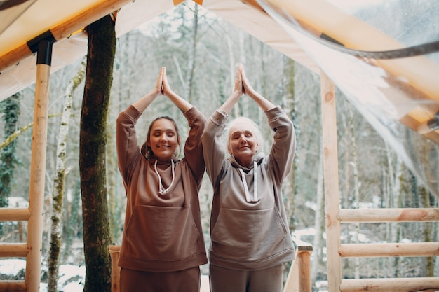 Woman senior and young relaxing at glamping camping tent outdoor women family elderly mother and young daughter doing yoga