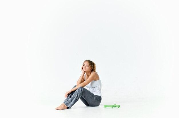 女性セロシュタノフは床に座り、背景にはダンベルがあります。高品質の写真