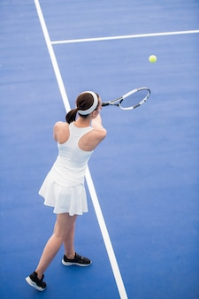 テニスコートでボールを提供する女性