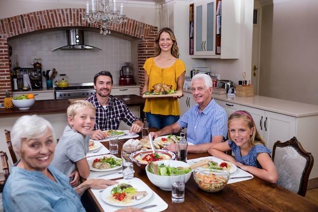 Женщина подает еду своей семье на кухне