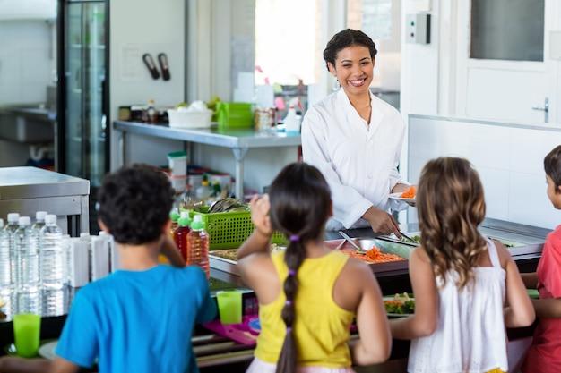 小学生に食べ物を提供する女性