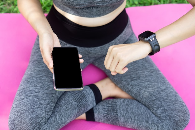 Woman setting smart watch and phone while doing yoga
