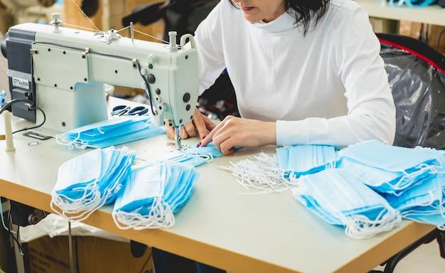 Женщина шьет лицевую медицинскую на швейной машине.