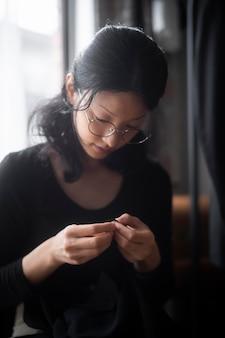 Женщина шьет вручную в помещении средний план Premium Фотографии