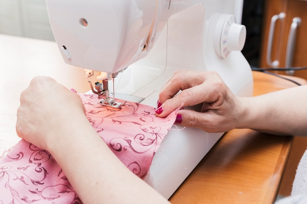 Woman sews cloth on a sewing machine over the wooden table