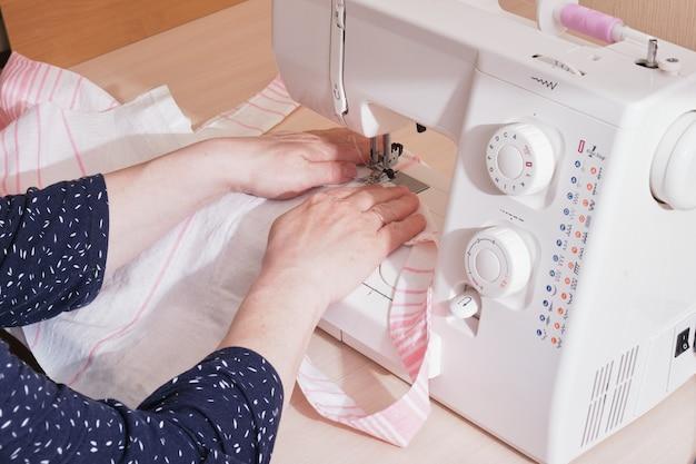 Женщина шьет хлопчатобумажную сумку на швейной машине, покупатель ткани