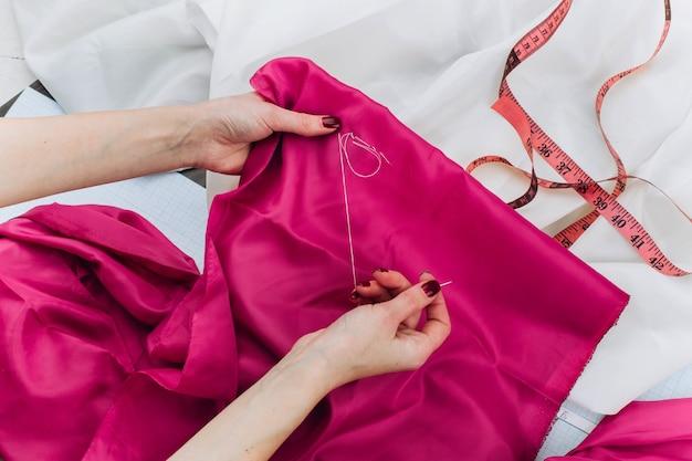 여자는 테이블에 어두운 분홍색 천을 바느질