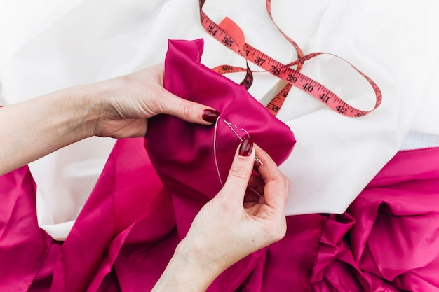 Woman sews dark pink cloth on the table