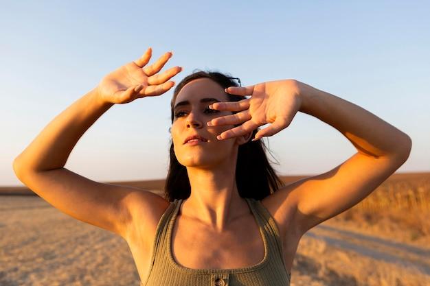 屋外で太陽から顔を陰で覆う女性