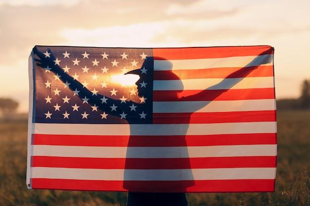 Силуэт тени женщины за американским флагом на закате. 4 июля день независимости сша концепции