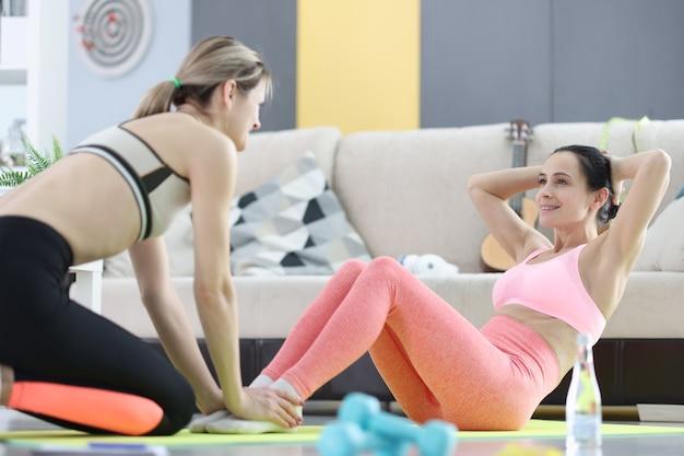 Женщина, качая пресс вместе с тренером дома. концепция регулярных спортивных мероприятий