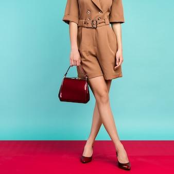 작은 빨간 핸드백과 검은 색 옻칠 하이힐 신발을 착용하는 여자 매끈한 다리. 보기 닫기