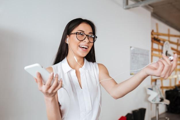 Женщина делит один наушник с кем-то для прослушивания музыки