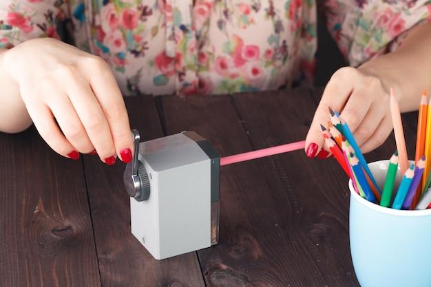 Женщина точит цветной карандаш