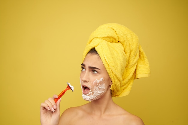 Woman shaves her face with a razor, hair removal, facial hair removal