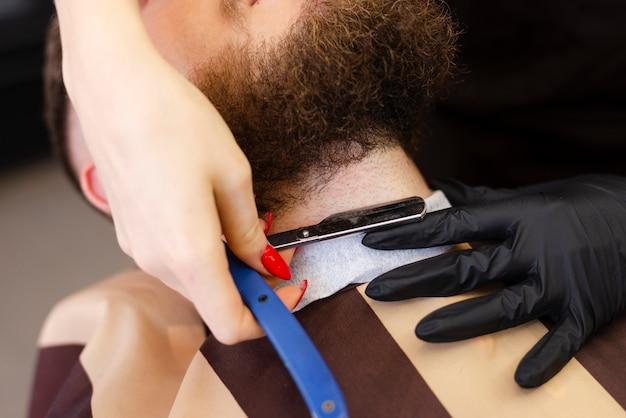 Женщина бреет бороду клиента крупным планом