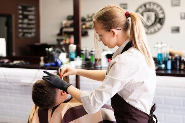 Женщина бреет бороду клиента
