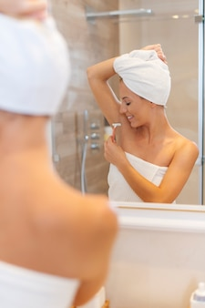 シャワーの後に脇の下を剃る女性