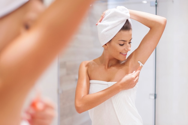 Woman shaving armpit in bathroom